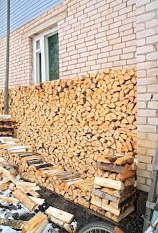 Brandhout in de buurt van muur van het landelijke gebouw