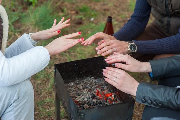 Brandhout in de grill en rode kolen met stroom die eruit komt. kleine jongen in rode jas verwarmt zijn bevroren handen boven de vlammen van de grill koperslager. picknick in de winter