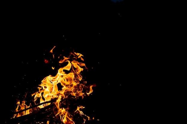Brandhout met vuurspatten, vlammen en rook.