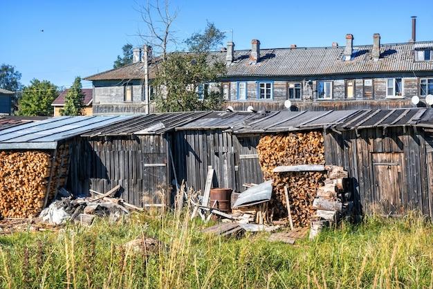 Brandhout onder het dak van een schuur op de solovetsky-eilanden en een houten woongebouw met ramen
