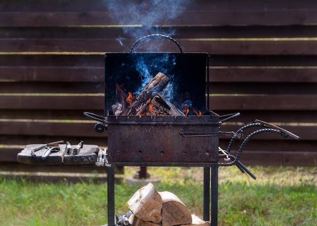 Brandhout verbranden en barbecueën buiten in de verharding.