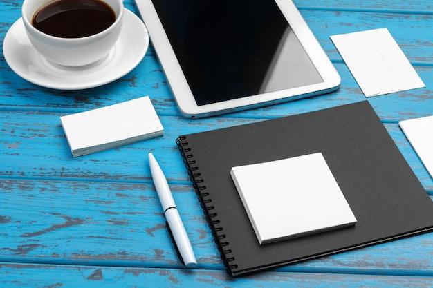 Branding briefpapier op blauw bureau. bovenaanzicht van papier, visitekaartje, notitieblok, pennen en koffie.