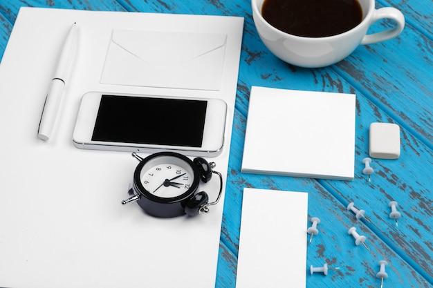 Branding kantoorbehoeftenmodel op blauw bureau. bovenaanzicht van papier, visitekaartje, notitieblok, pennen en koffie.