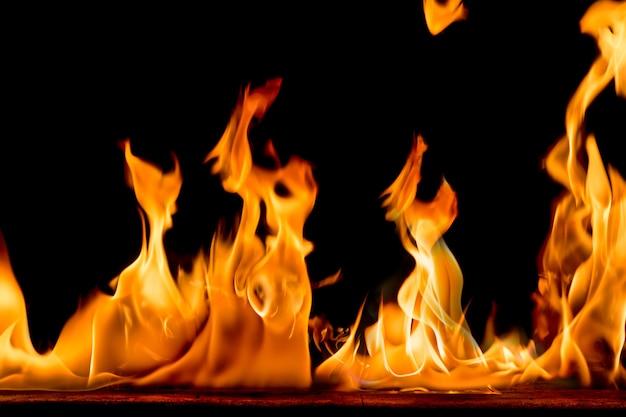 Brandvlammen op zwarte achtergrond. helder en kleurrijk vuur tegen een zwarte nacht.