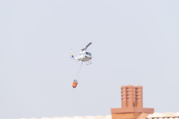 Brandweer-noodhelikopter voert een vlucht bij het tanken van water uit in een stedelijk gebied