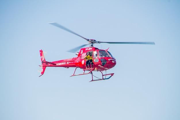 Brandweerhelikopter in rio de janeiro, brazilië - 24 april 2021: brandweerhelikopter vliegt over het strand van copacabana in rio de janeiro.