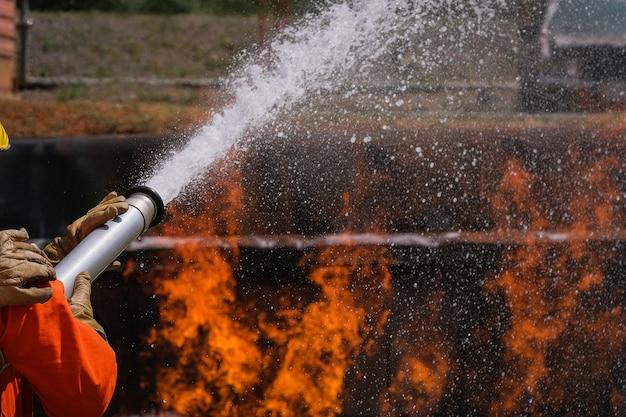 Brandweerlieden blussen de brand met een chemisch schuim dat via een lange slang uit de brandweerauto komt.