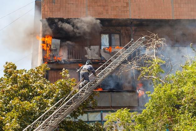 Brandweerlieden blussen een brand in een hoogbouwgebouw.