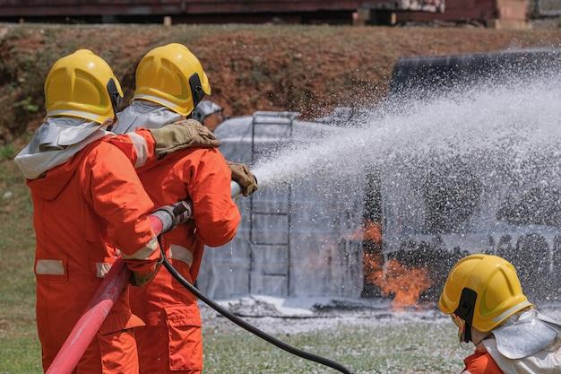 Brandweerlieden blussen het vuur met een chemisch schuim dat uit de brandweerwagen komt via een lange slang.