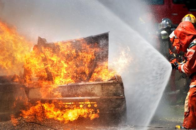 Brandweerlieden die brandblusapparaat en water gebruiken voor jachtvuur tijdens firefight training.