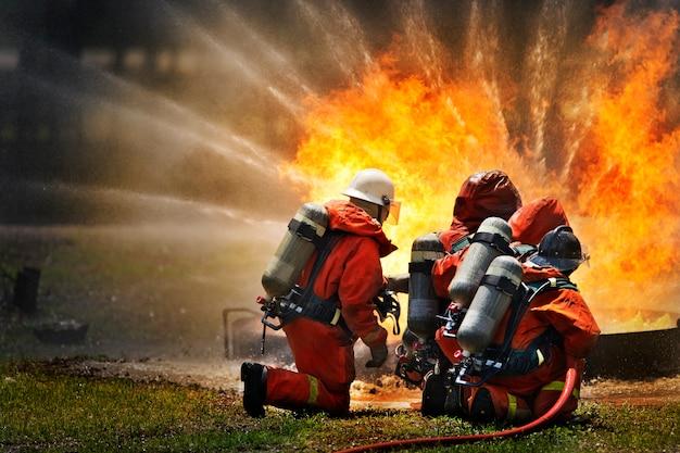 Brandweerlieden die brandbluswater gebruiken om vuur te bestrijden tijdens de training.