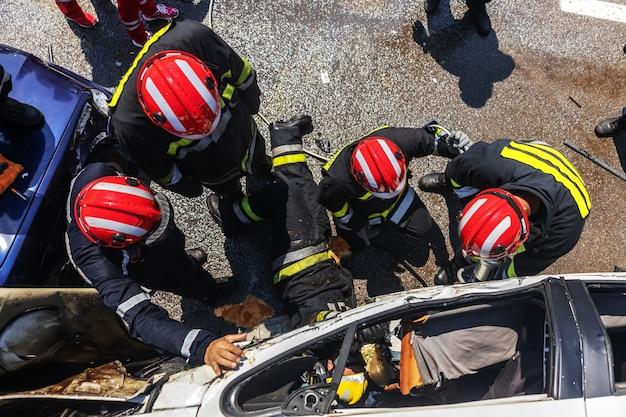 Brandweerlieden die de man uit de gecrashte auto proberen te bevrijden. er is een gecrashte auto bij auto-ongeluk.