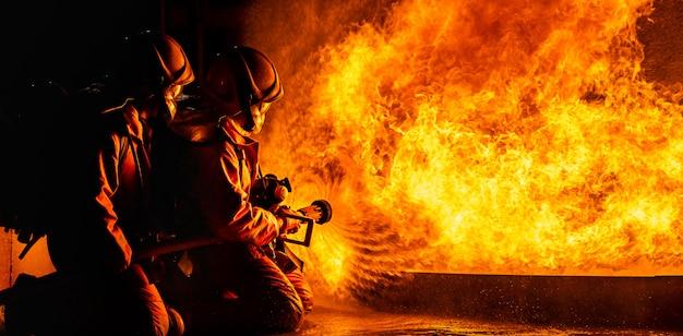 Brandweerlieden die 's nachts vlammen spuiten
