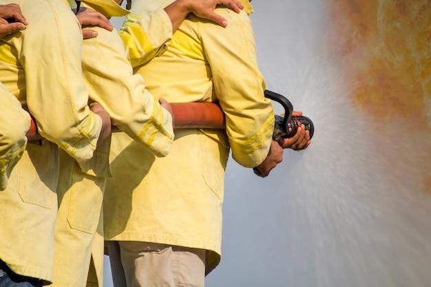 Brandweerlieden die water uit slang gebruiken voor brandbestrijding bij brandbestrijdingstraining van verzekeringsgroep. brandweerman draagt een brandweerpak voor veiligheid onder het geval van gevaarstraining.