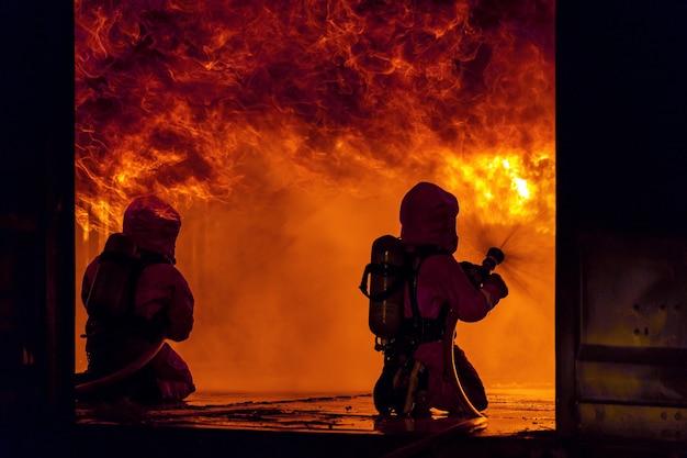 Brandweerlieden die watermistbrandblusser gebruiken om met de vuurvlam in een groot gebouw te vechten.