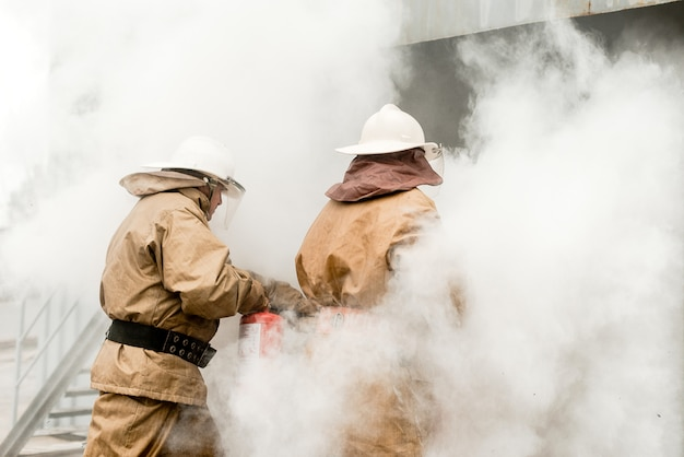 Brandweerlieden gebruiken brandblussers tijdens een training om te stoppen met vuur in een gevaarlijke missie
