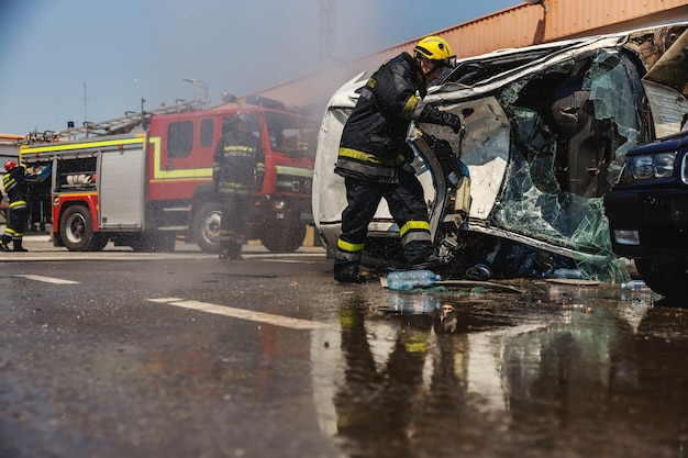 Brandweerlieden in actie. brandweerlieden die brand blussen en proberen om de gecrashte auto om te keren bij een auto-ongeluk.