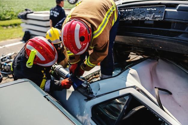 Brandweerlieden proberen de mens uit de gecrashte auto te bevrijden. er is een gecrashte auto bij auto-ongeluk.