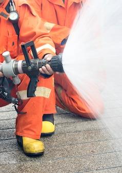 Brandweerlieden sproeien water om een brand te stoppen