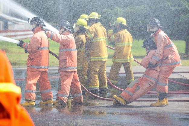 Brandweerlieden spuiten water in brandblussers en redden levens bij het benzinestation.