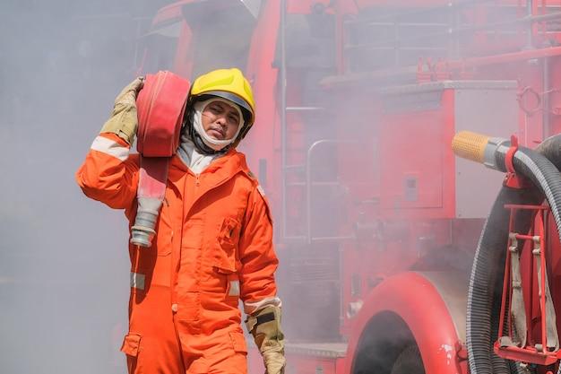 Brandweerlieden trainen, teamoefening om te vechten met vuur in noodsituaties. een brandweerman draagt een waterslang die door vlam loopt