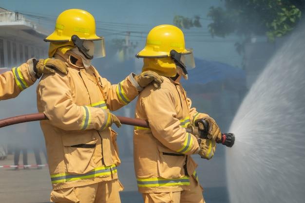 Brandweerlieden training met waterslang