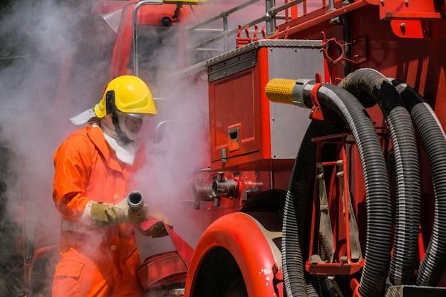 Brandweerlieden training, teamoefening om in noodsituaties met brand te bestrijden. een brandweerman maakt een slang vast aan het brandweervoertuig