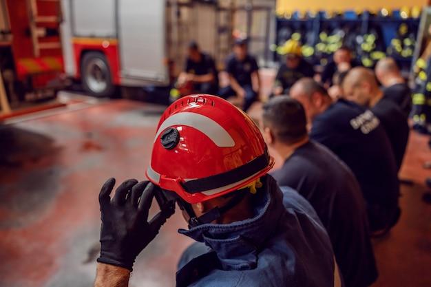 Brandweerlieden zitten in een cirkel en nemen een pauze van een moeilijke dag.