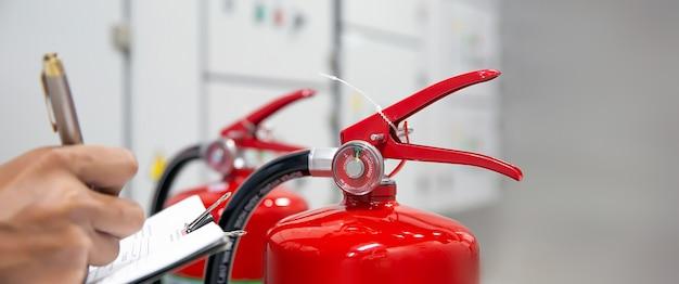 Brandweerman controleert manometer van rode brandblustank in het gebouw