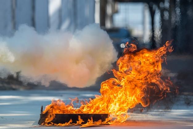 Brandweerman die gebruik een brandblusapparaat op een opleidingsbrandkraan met witte rook toont. arbo-concept.
