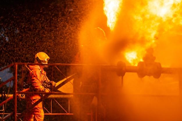 Brandweerman die watermist gebruikt om te vechten met de vlam van het lek van de oliepijpleiding
