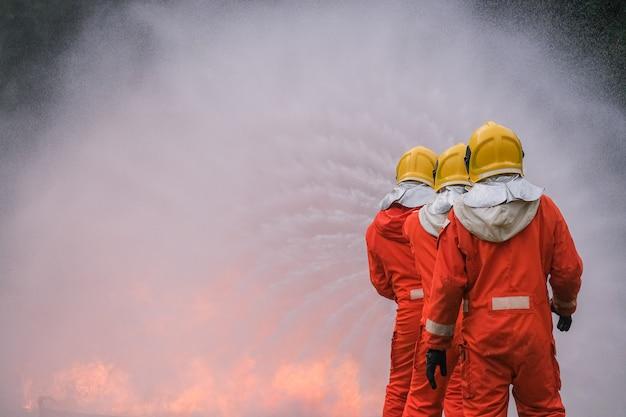 Brandweerman gebruikt water bij brandbestrijding
