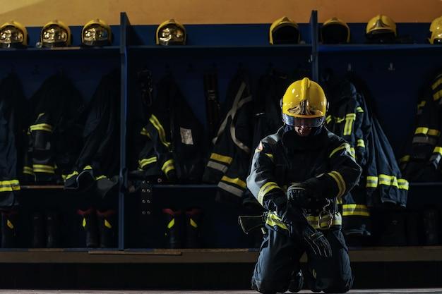 Brandweerman in beschermend uniform geknield en handschoenen op het hoofd aantrekken en zich voorbereiden op actie.