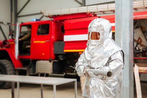 Brandweerman in een speciaal folie beschermend pak met een brandweerwagen op de achtergrond