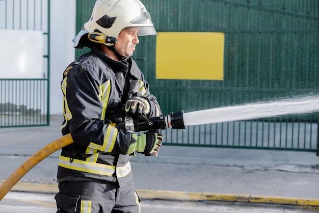 Brandweerman met een slang die water in een brand verspreidt