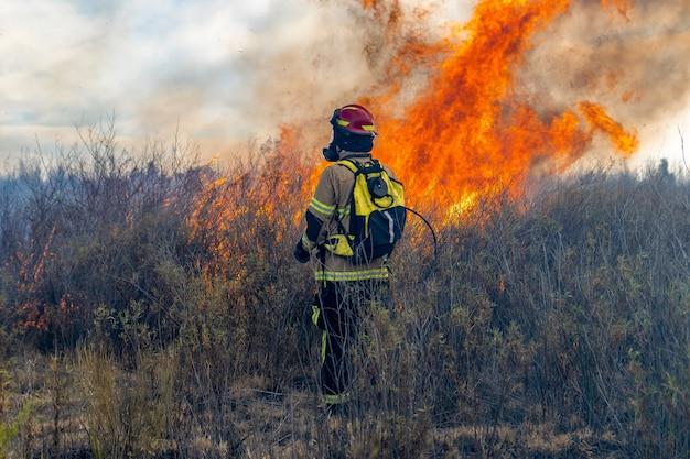 Brandweerman probeert een bosbrand te blussen