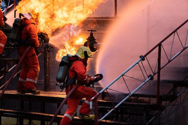 Brandweermansteam dat watermist-type brandblusser gebruikt om te vechten met de vlam van oliepijplijnlek en explosie op booreiland en aardgasstation. brandweerman en industrieel veiligheidsconcept.