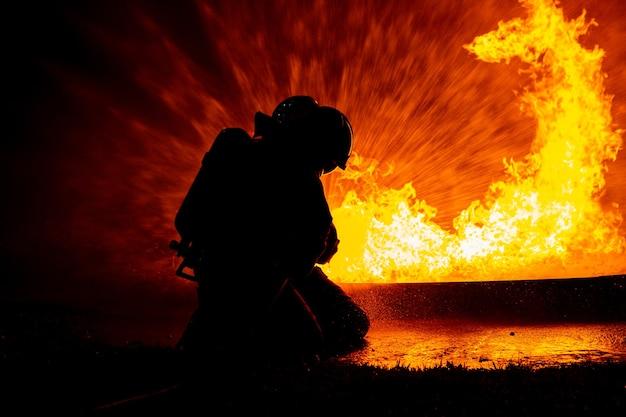 Brandweeroperatieteam dat water gebruikt voor het verminderen van brandsprinklervernietiging