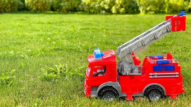 Brandweerwagen speelgoed op groen gras. speelgoed. kopieer ruimte