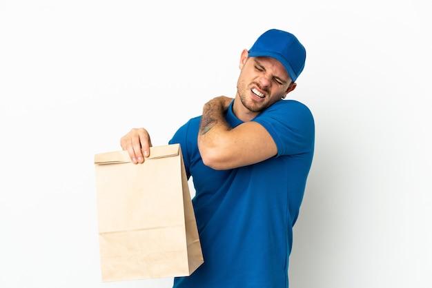 Braziliaan die een zak met afhaalmaaltijden neemt geïsoleerd op een witte achtergrond die lijdt aan pijn in de schouder omdat hij moeite heeft gedaan