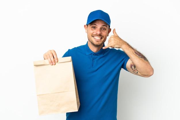 Braziliaans die een zak afhaalmaaltijden neemt die op witte achtergrond wordt geïsoleerd en telefoongebaar maakt. bel me terug teken