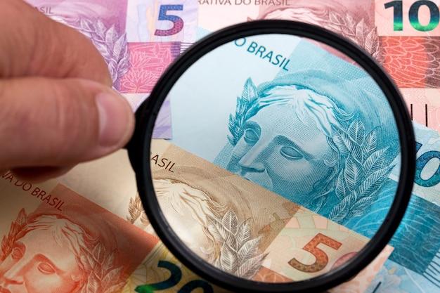 Braziliaans geld in een vergrootglas een bedrijfsachtergrond