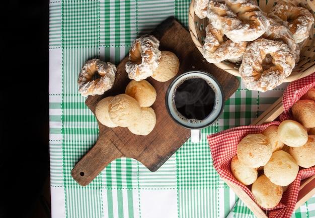 Braziliaans kaasbrood en zoet koekje en een kopje koffie op een tafel met groen geruit tafelkleed, selectieve focus.