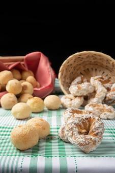 Braziliaans kaasbrood en zoet koekje op een tafel met groen geruit tafelkleed, selectieve focus.