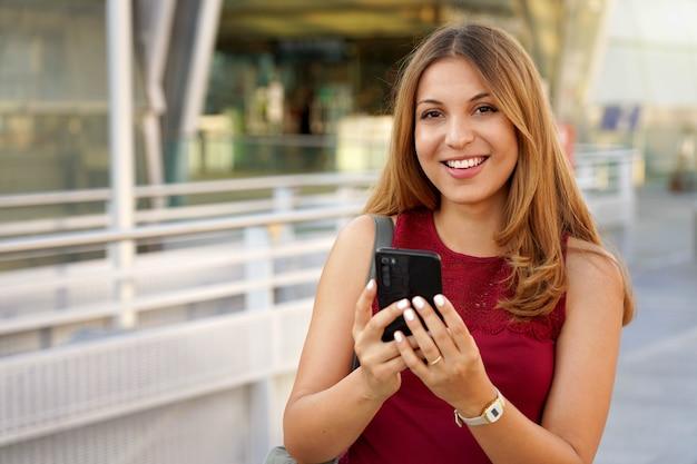 Braziliaans meisje met smartphone in de buurt van metrostation. vrolijke jonge vrouw chatten met mobiele telefoon camera buitenshuis kijken.