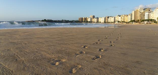 Braziliaans strand met voetafdrukken in het zand en wilde golven van de oceaan op een zonnige zomerdag