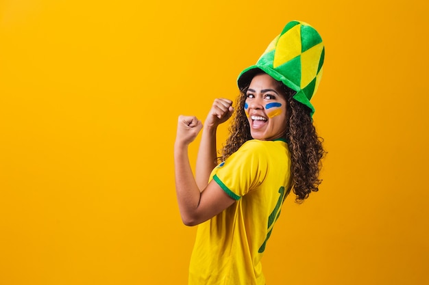 Braziliaanse aanhanger. braziliaanse vrouw fan vieren op voetbal of voetbalwedstrijd op gele achtergrond. brazilië kleuren. ja!
