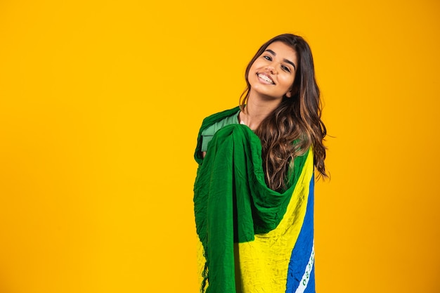 Braziliaanse aanhanger. braziliaanse vrouw fan vieren op voetbal of voetbalwedstrijd op gele achtergrond. brazilië kleuren.