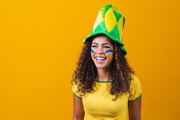 Braziliaanse aanhanger. braziliaanse vrouw fan vieren op voetbal of voetbalwedstrijd op gele achtergrond met kopie ruimte. brazilië kleuren.
