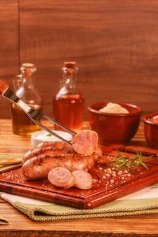 Braziliaanse bbq-vork die varkensworst serveert